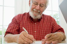 An older man fills out a paper survey