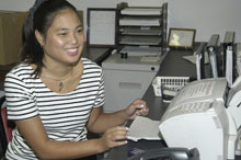 Adult woman with a developmental disability smiles while working in an office
