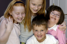 Four smiling children, including one with a developmental disability