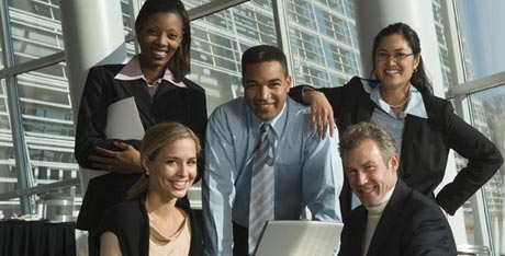 Group of five smiling executives posing in front of office window