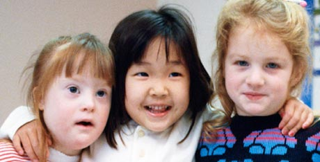 Portrait of three smiling children, one of whom is developmentally  disabled