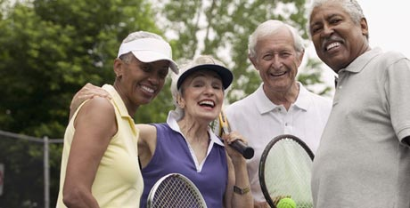 Portrait of two older couples after a game of tennis