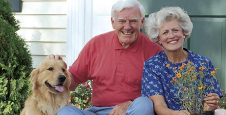 Portrait of an older couple outdoors with their dog
