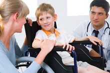 A child in a wheelchair speaking with his mother and his doctor