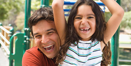 Father and daughter laughing together in playground