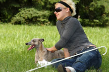 Blind woman relaxes with her service animal in a park