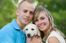 Happy couple poses with their pet dog